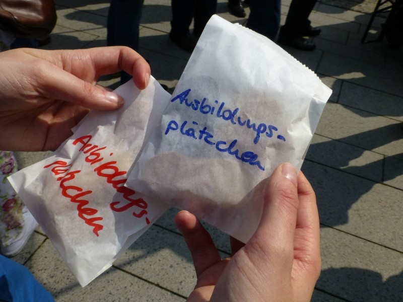 """Die Arbeitsgemeinschaft der Jungsozialistinnen und Jungsozialisten in der Sozialdemokratische Partei Deutschlands (Jusos) verteilen """"Ausbildungsplätzchen"""" bei der Maikundgebung in Essen, Foto von Anne Hemeda am 1. Mai 2014."""